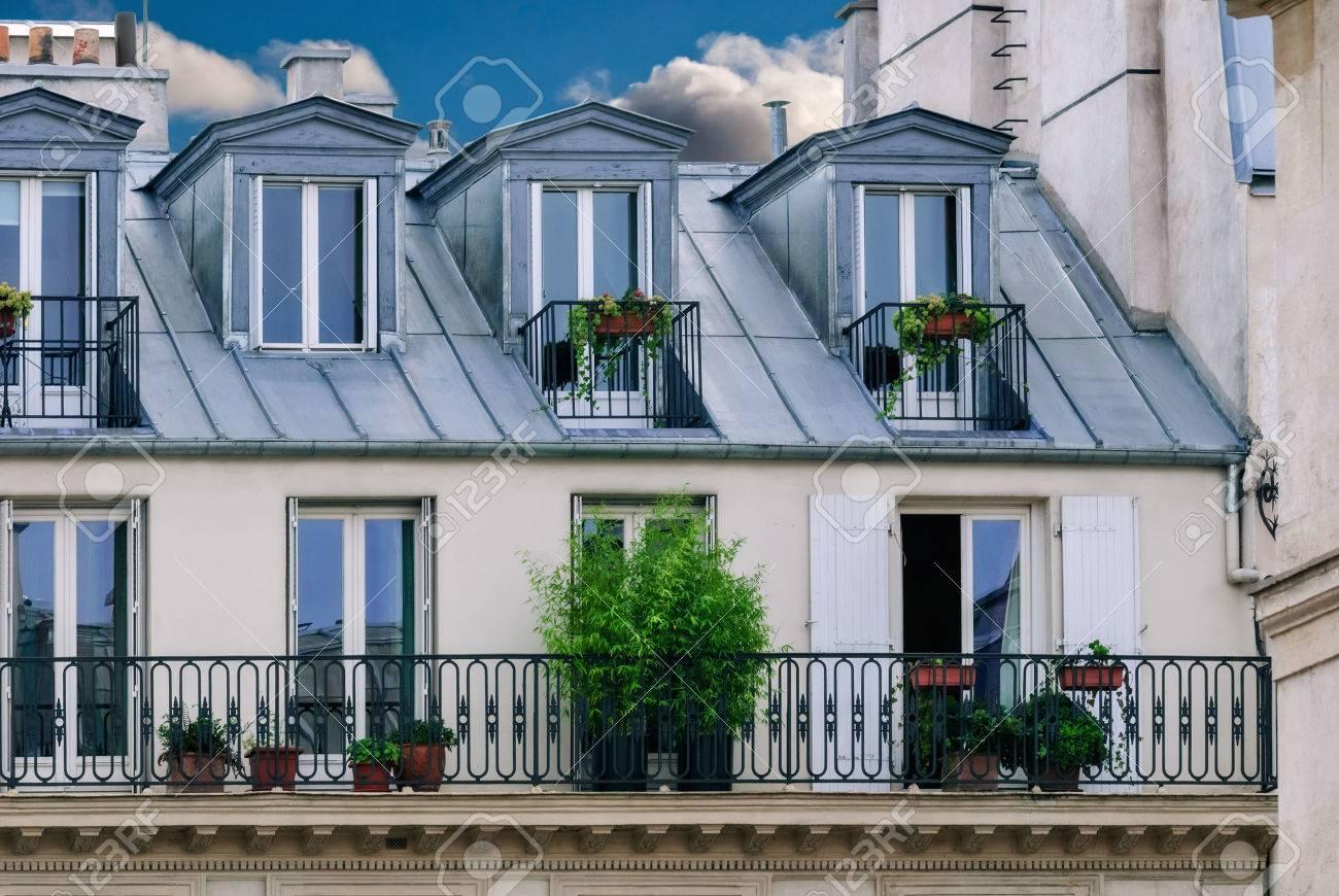 Standard Bild   Teil Des Hauses In Paris Mit Dachbodenzimmer Auf Dem Dach  Und Einem Balkon Mit Grün Und Blumen Verziert.