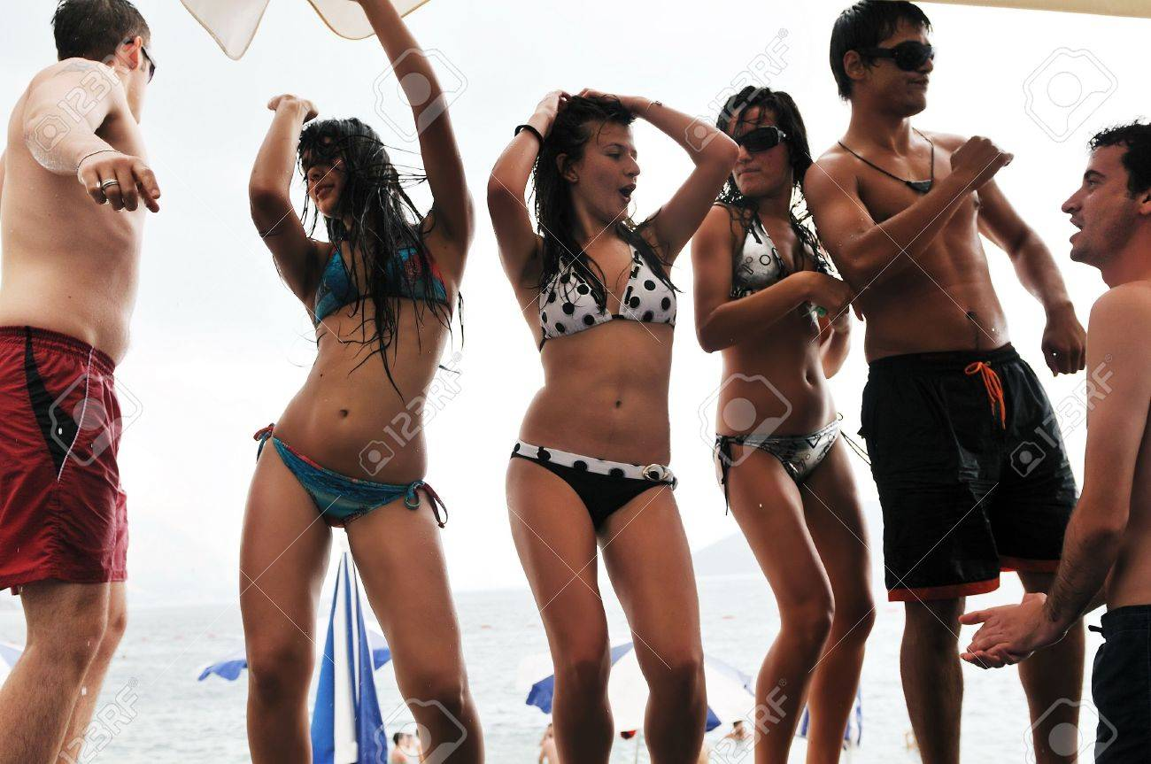 young happy people have fun and dancing on beach at sumer time with rain Stock Photo - 5387030
