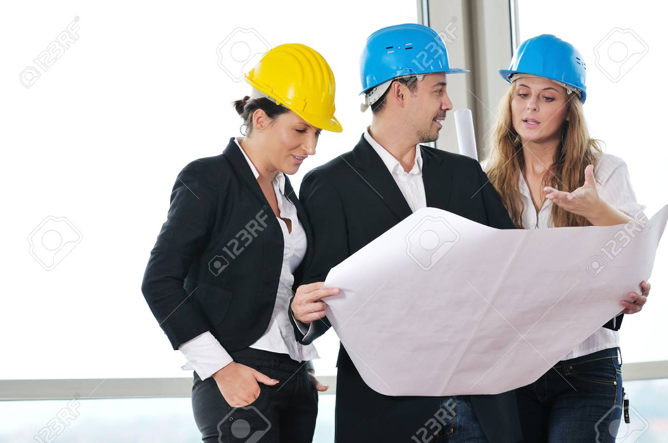 young arhitect group in big bright modern new apartment looking blueprints and building plans Stock Photo - 6141419