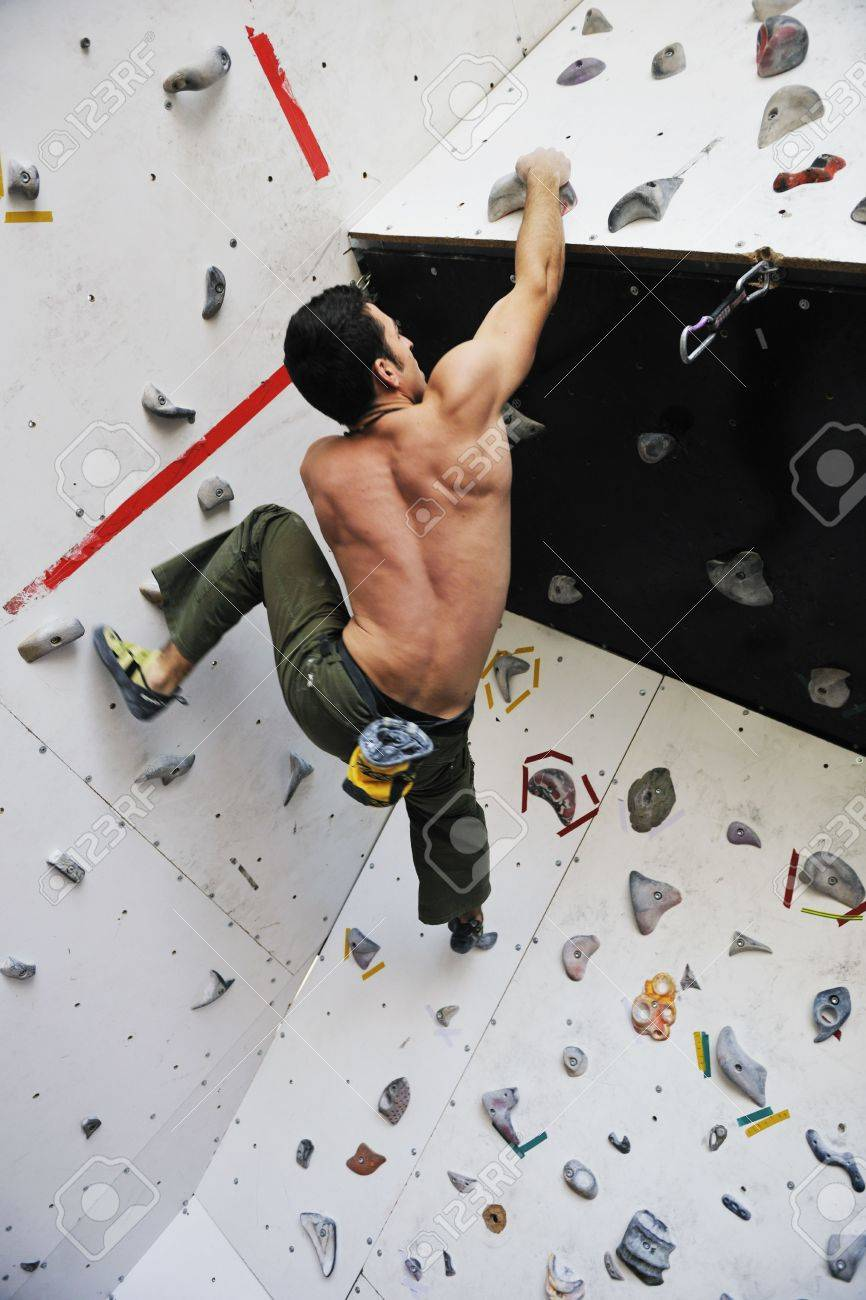 young and fit man exercise free mountain climbing on indoor practice wall Stock Photo - 6322100