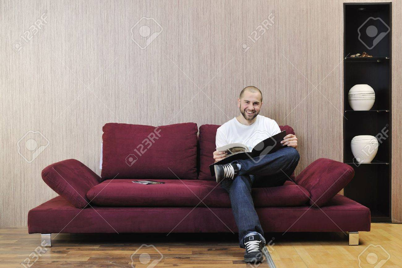 happy smling young man reading newspaper and relaxing in modern living room with fancy furniture and sofa Stock Photo - 6667149
