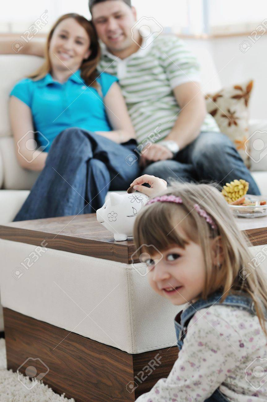 young parrent at home with beautiful child make savings and put coins money in piggy bank Stock Photo - 6742358