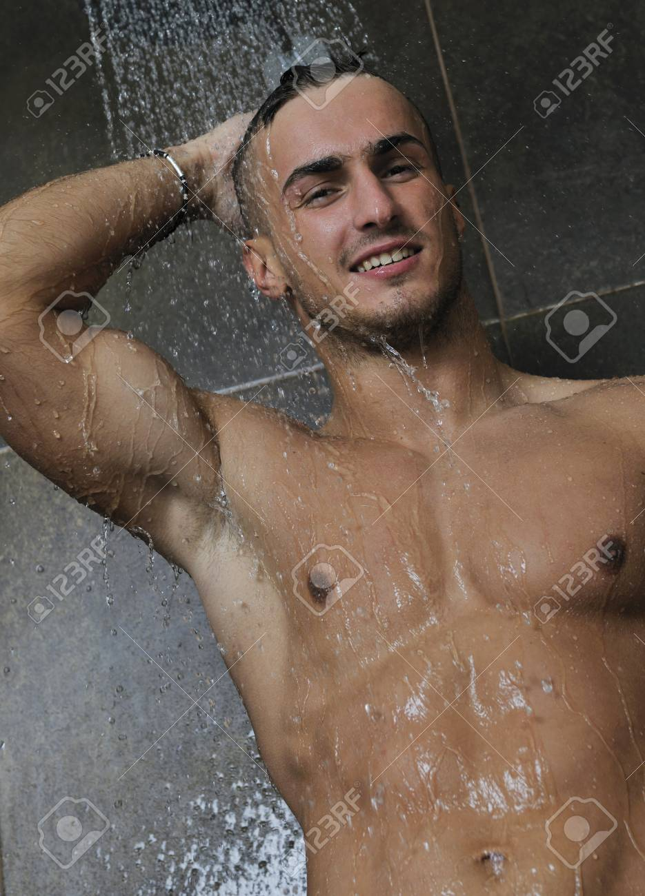 young good looking and attractive man with muscular body wet taking showe in bath with black tiles in background Stock Photo - 7286135
