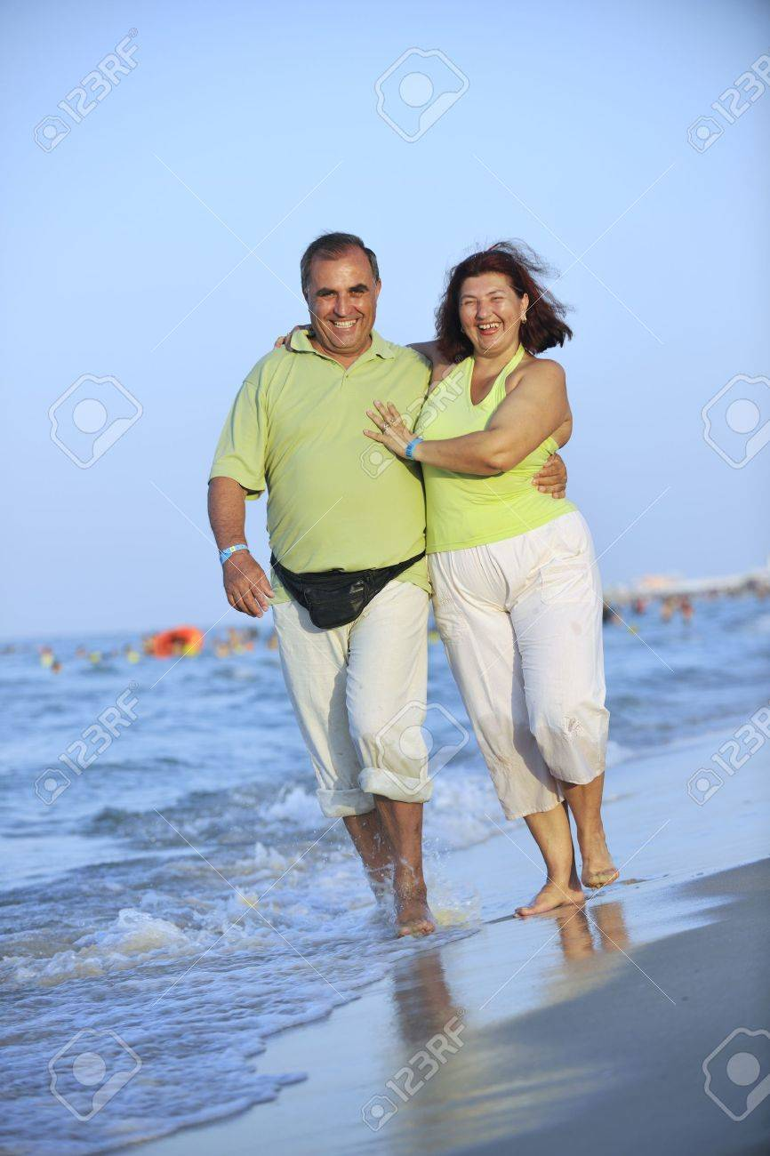 happy senior mature elderly people couple have romantic time on beach at sunset Standard-Bild - 7615345