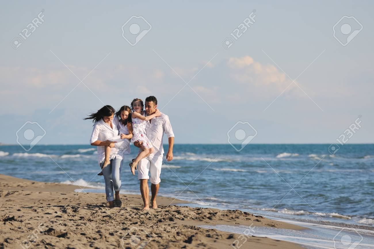 happy young family in white clothing have fun at vacations on beautiful beach Stock Photo - 8236470