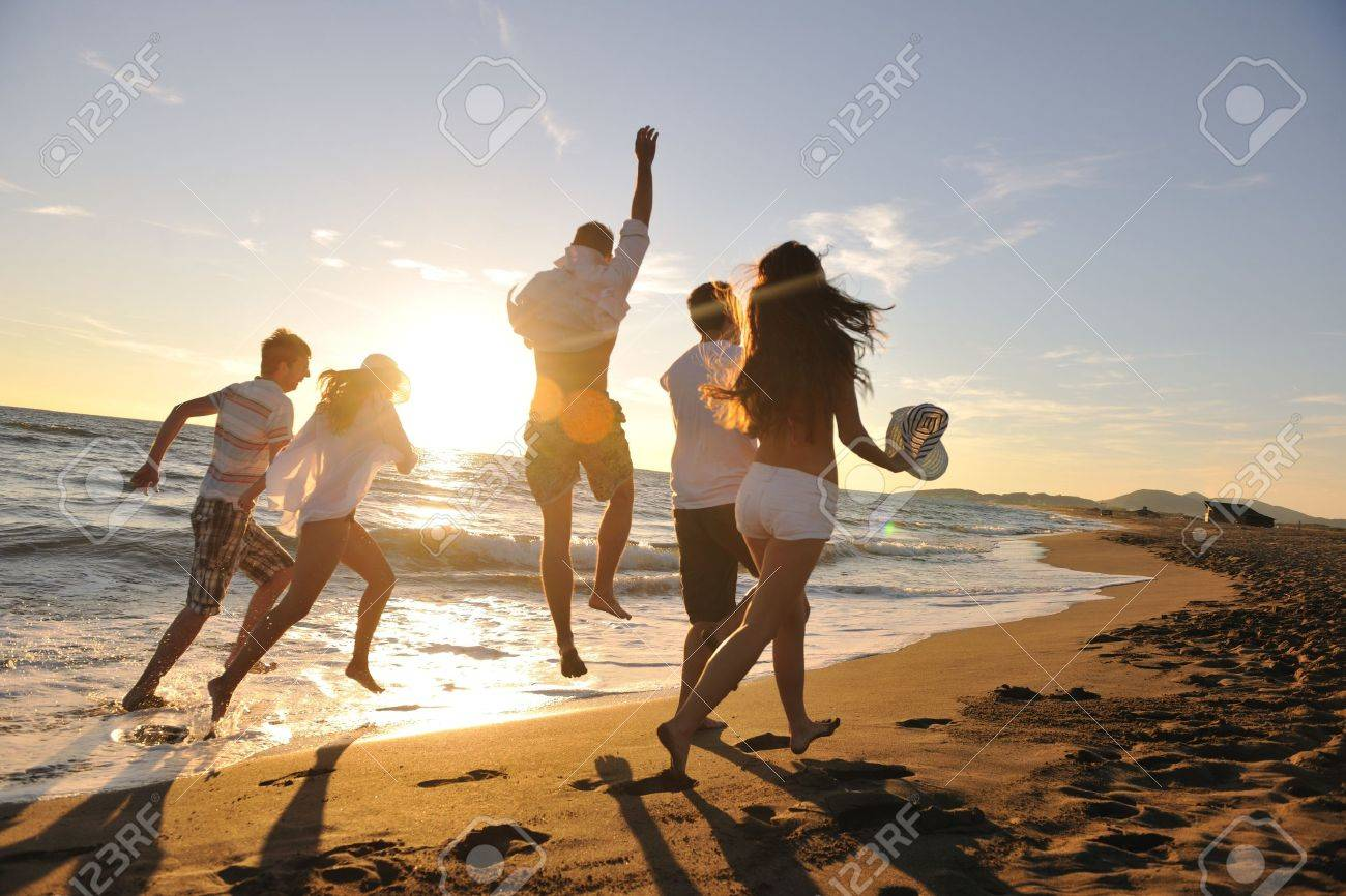 happy young people group have fun white running and jumping on beacz at sunset time Stock Photo - 8237485