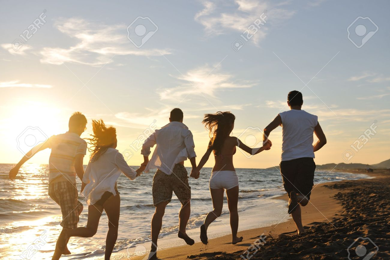 happy young friends group have fun and celebrate while jumping and running on the beach at the sunset Stock Photo - 8236482