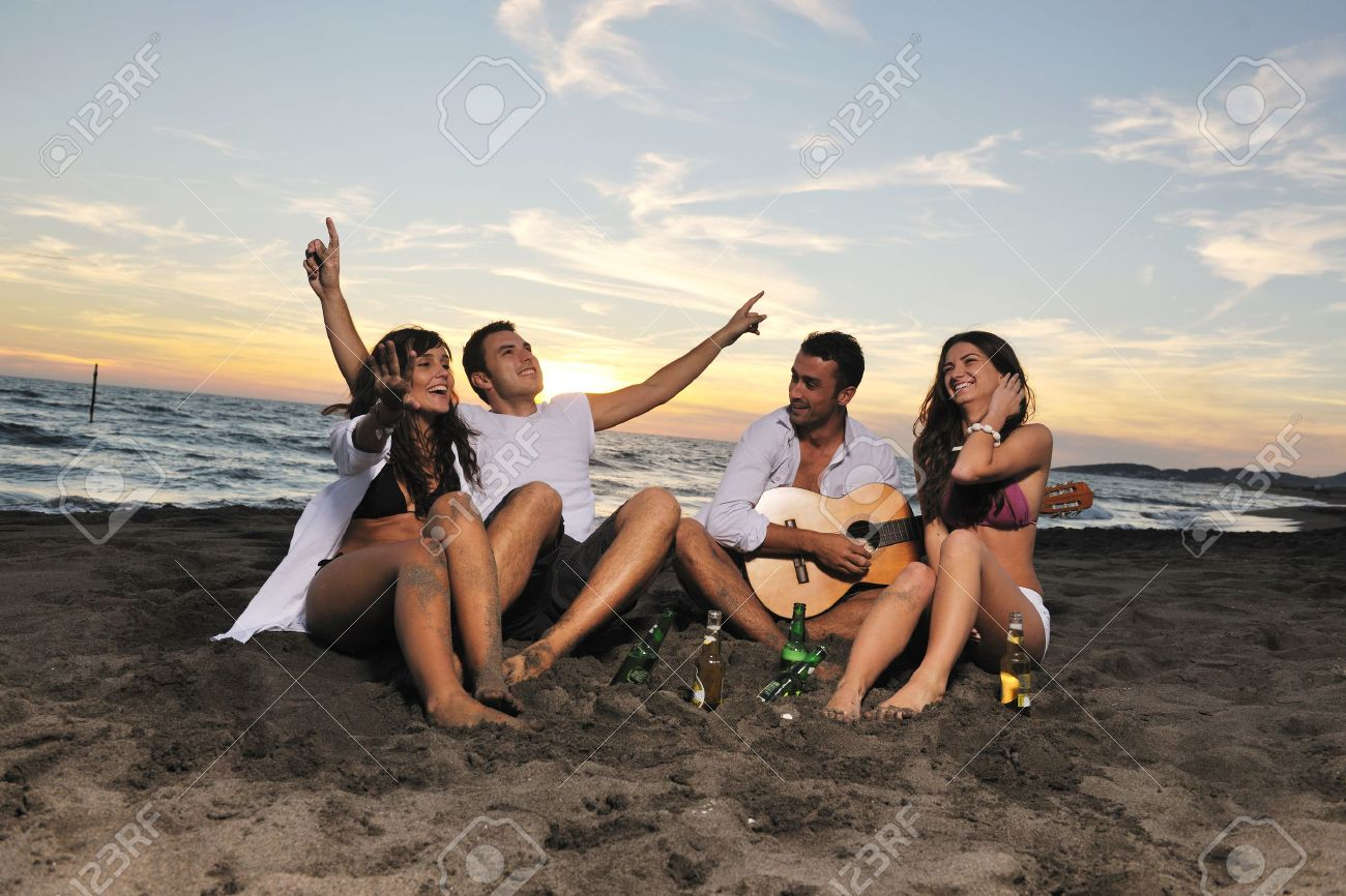 happy young friends group have fun and celebrate while jumping and running on the beach at the sunset Stock Photo - 8237750