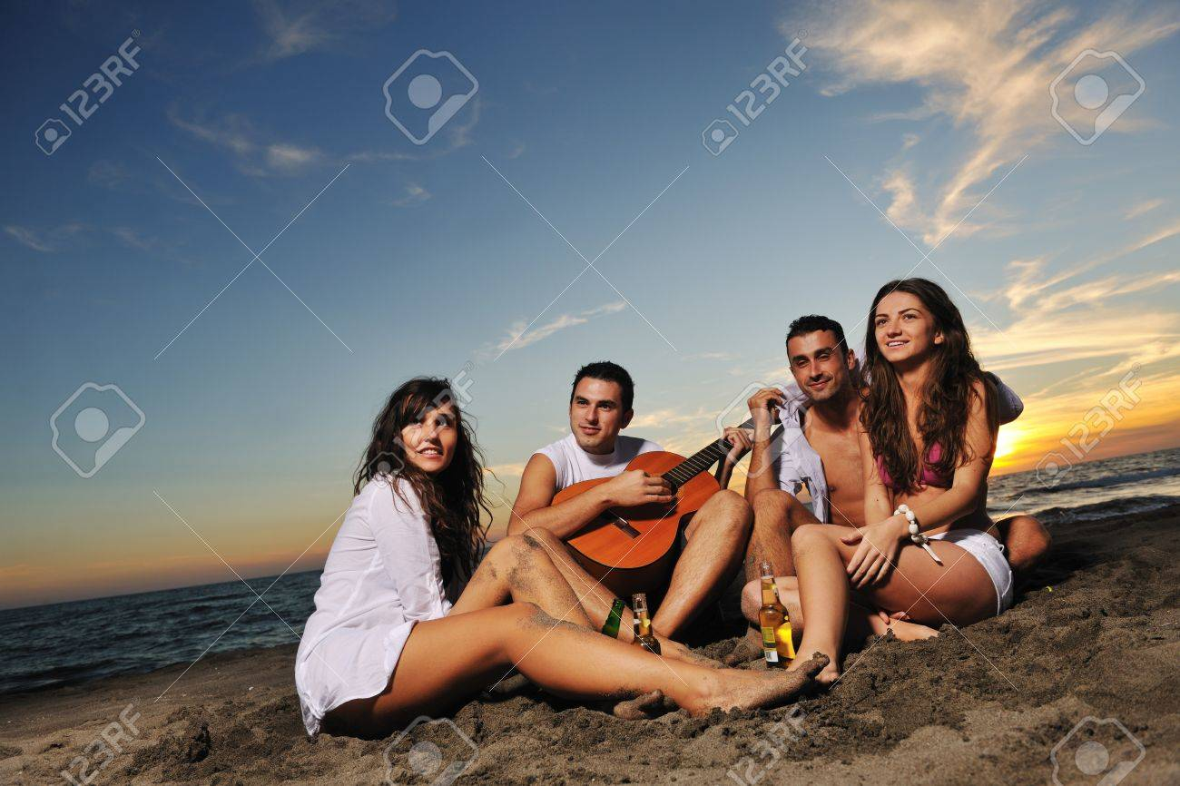happy young friends group have fun and celebrate while jumping and running on the beach at the sunset Stock Photo - 8327742