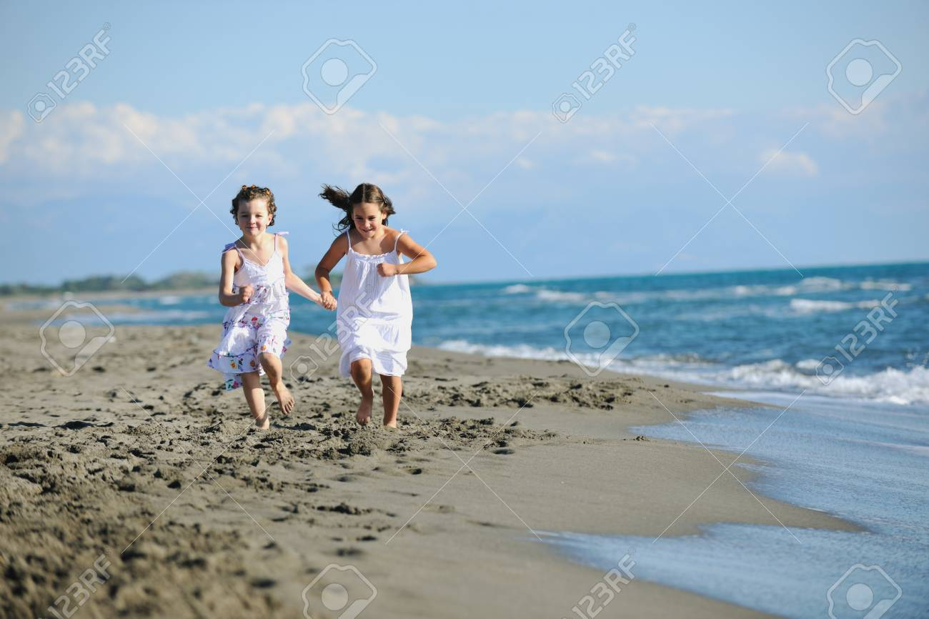 happy two little girls have fun and joy time at beautiful beach while running from joy Stock Photo - 8327987