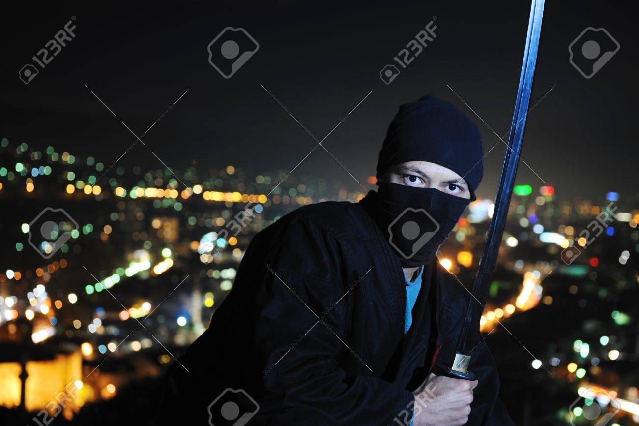 ninja assasin hold katana samurai old martial weapon swordat night with city lights in background Stock Photo - 8328031