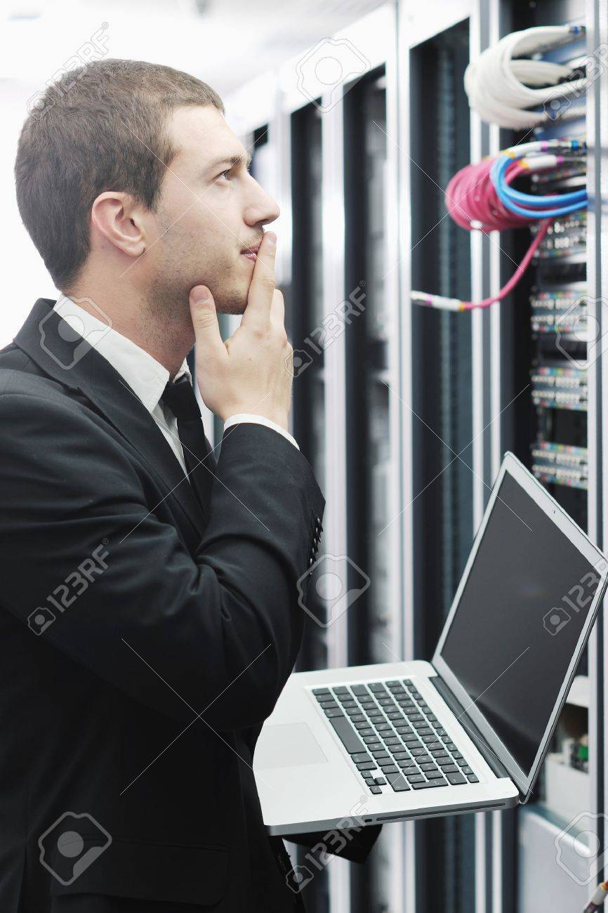 young it  engeneer business man with thin modern aluminium laptop in network server room Stock Photo - 8769094