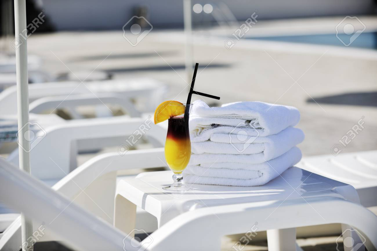 coctail dring with orange att sunny day on swimming pool side with white towel decoraton Stock Photo - 8881478