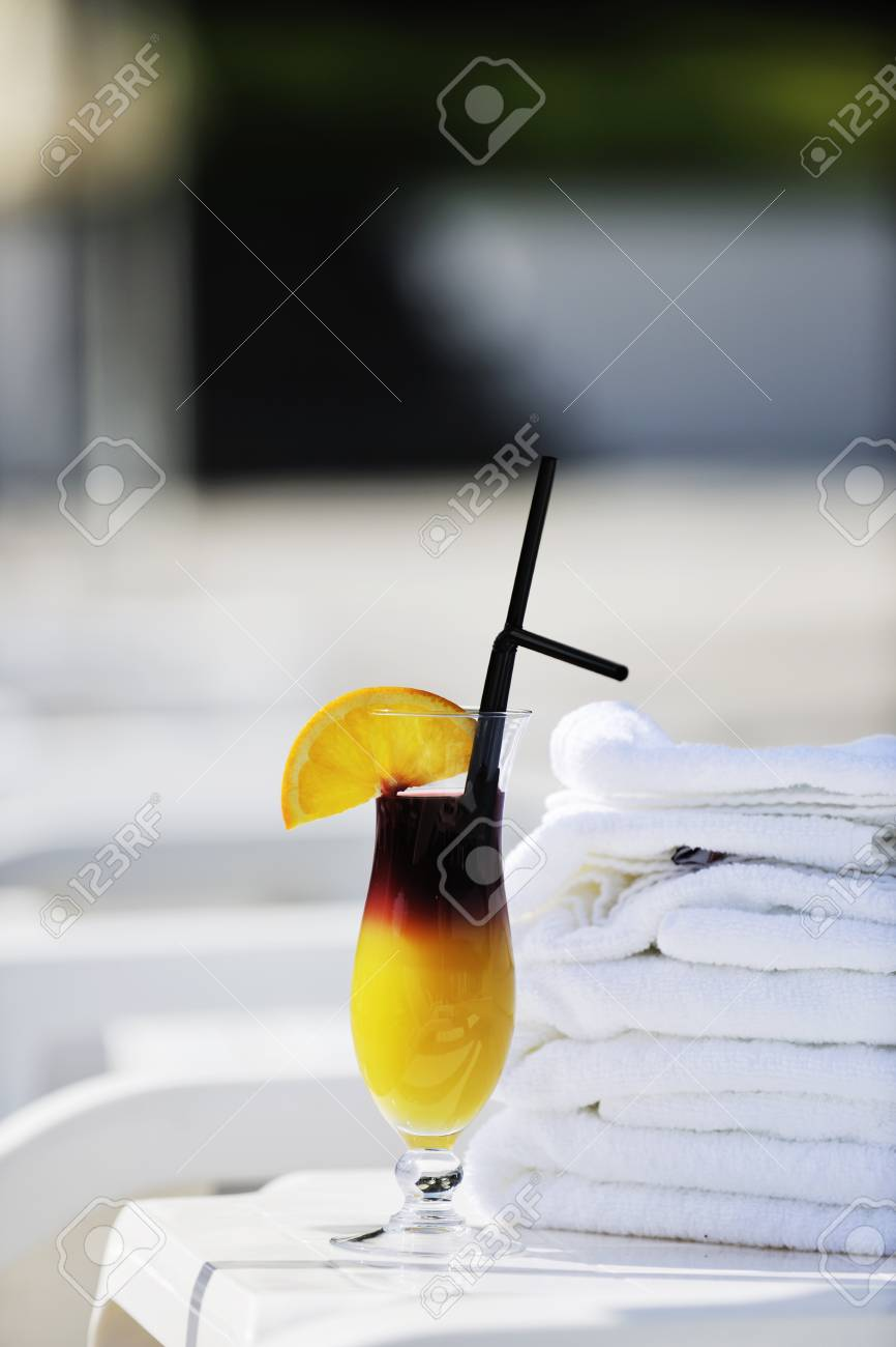 coctail dring with orange att sunny day on swimming pool side with white towel decoraton Stock Photo - 8881502