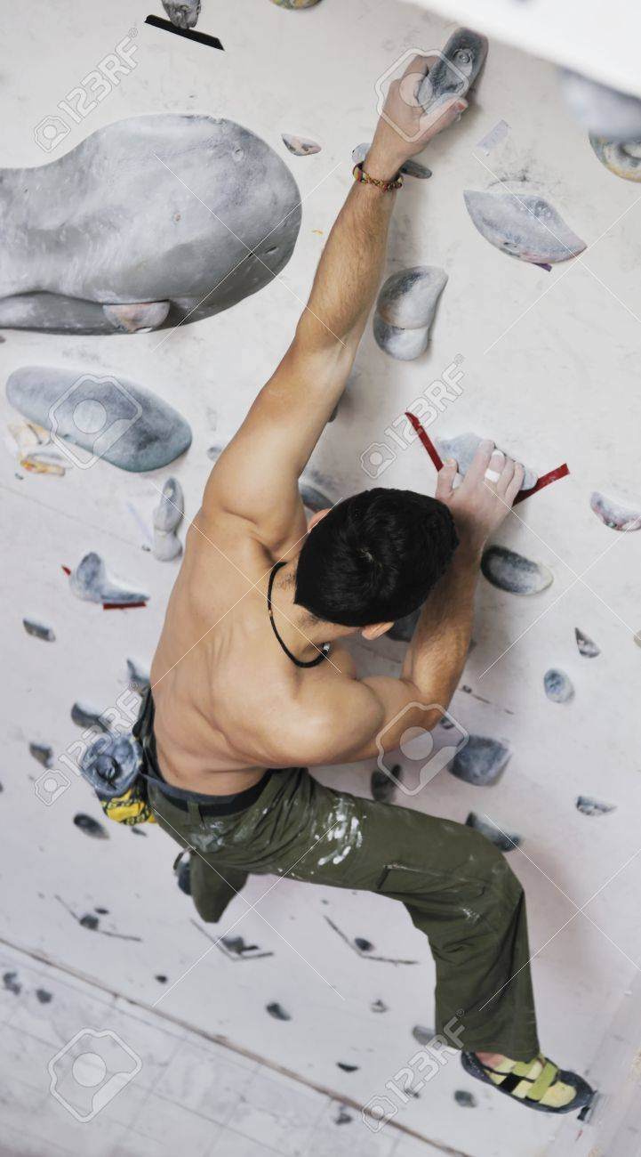 young and fit man exercise free mountain climbing on indoor practice wall Stock Photo - 9549182