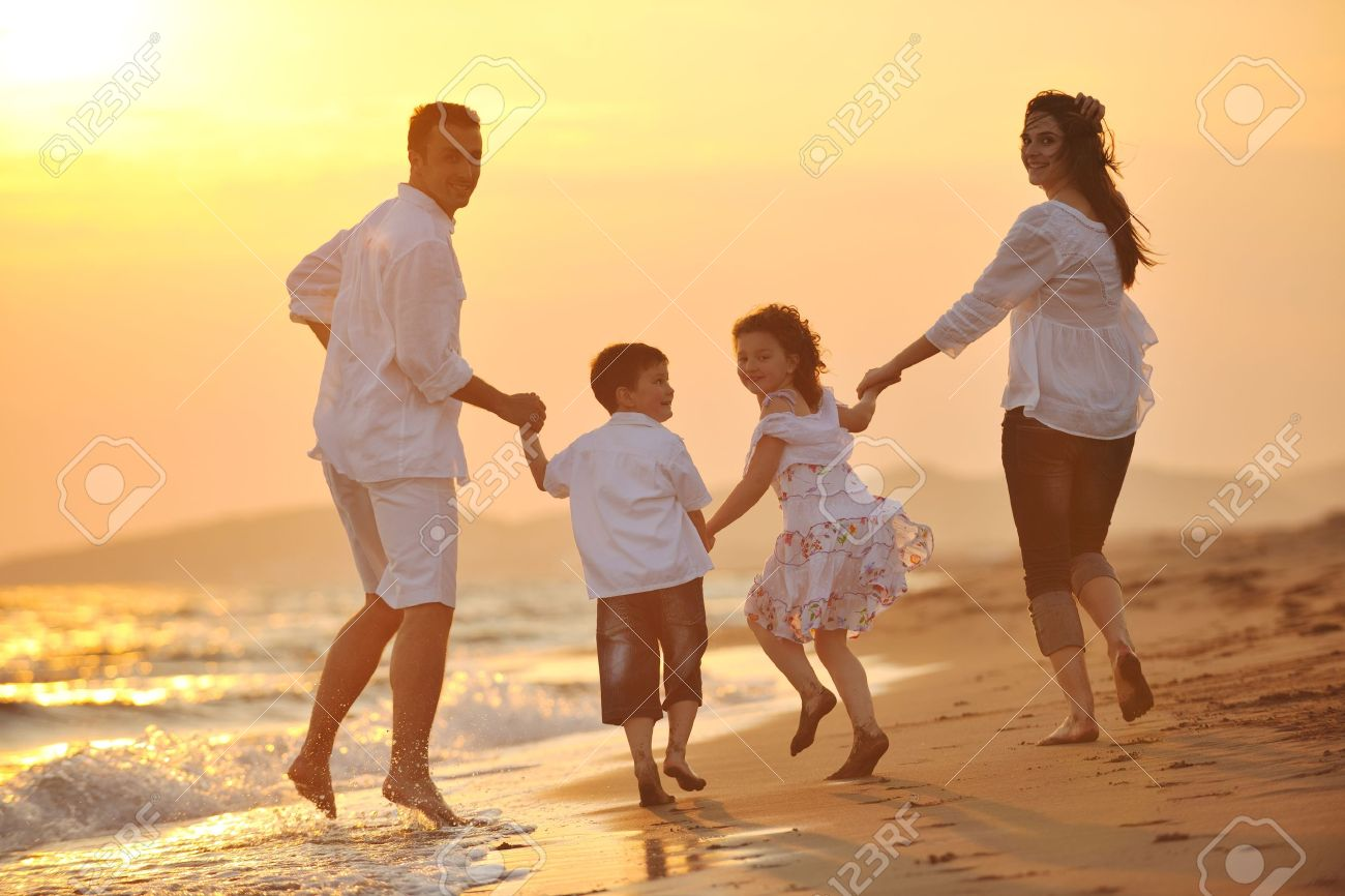 happy young family have fun on beach run and jump  at sunset Stock Photo - 9716052