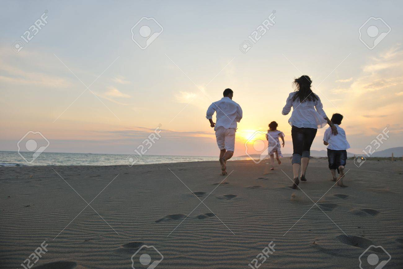 happy young family have fun on beach run and jump  at sunset Stock Photo - 9717687