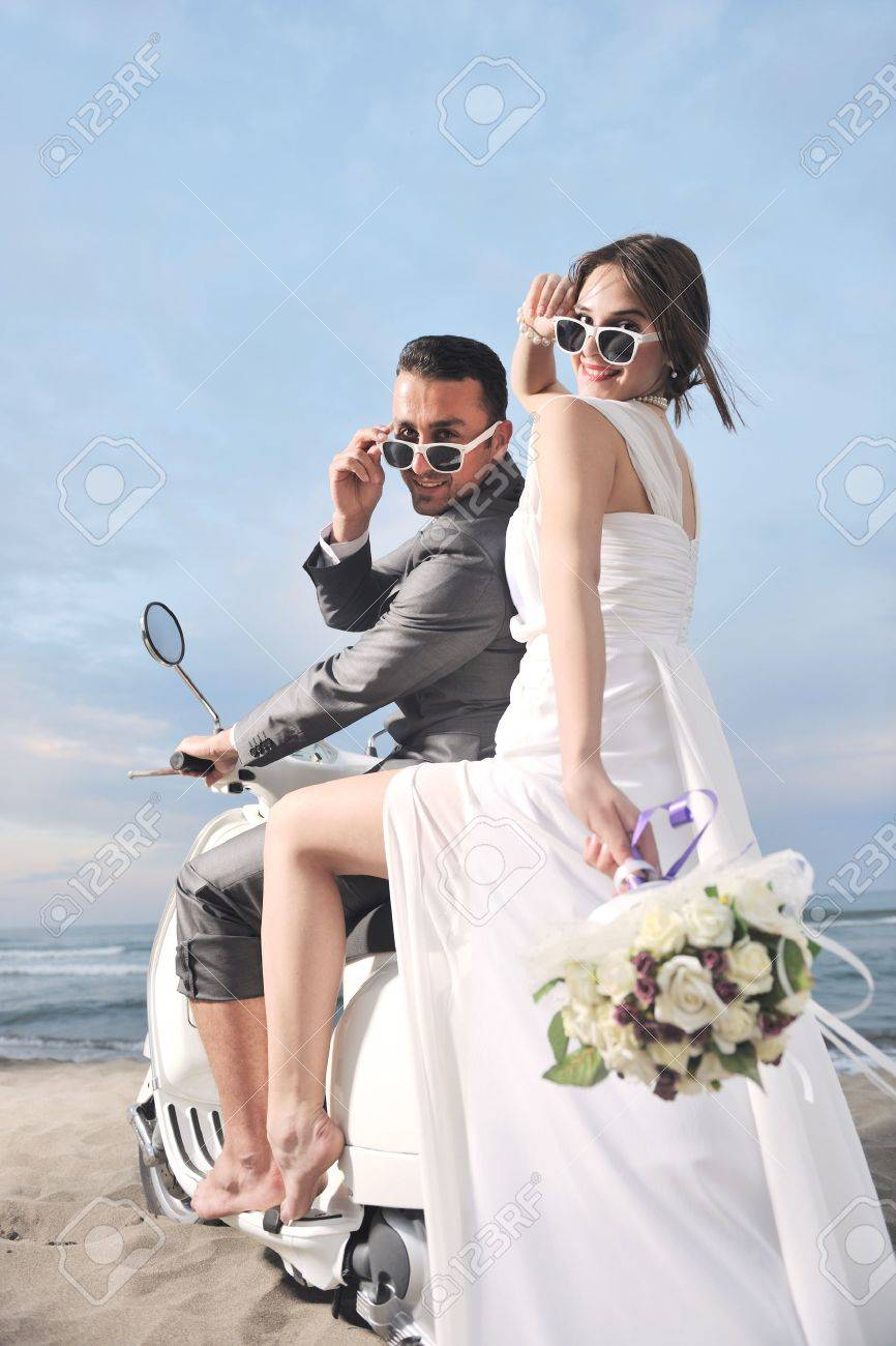 wedding scene of bride and groom just married couple on the beach ride white scooter and have fun Stock Photo - 9770561