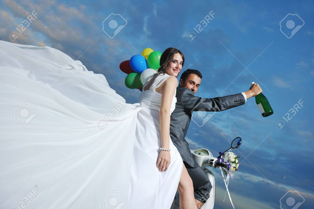 wedding sce of bride and groom just married couple on the beach ride white scooter and have fun Stock Photo - 9878530