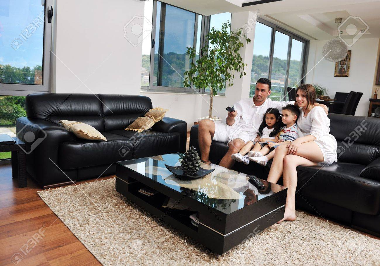 happy young family wathching flat tv at modern home indoor Stock Photo - 13270821