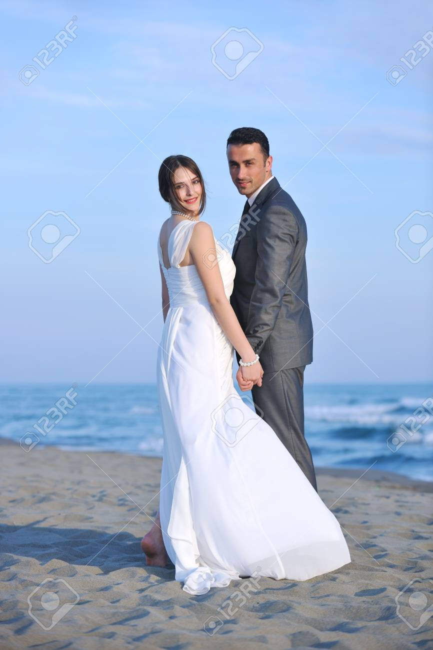 happy just married young couple celebrating and have fun at beautiful beach sunset Stock Photo - 9726427