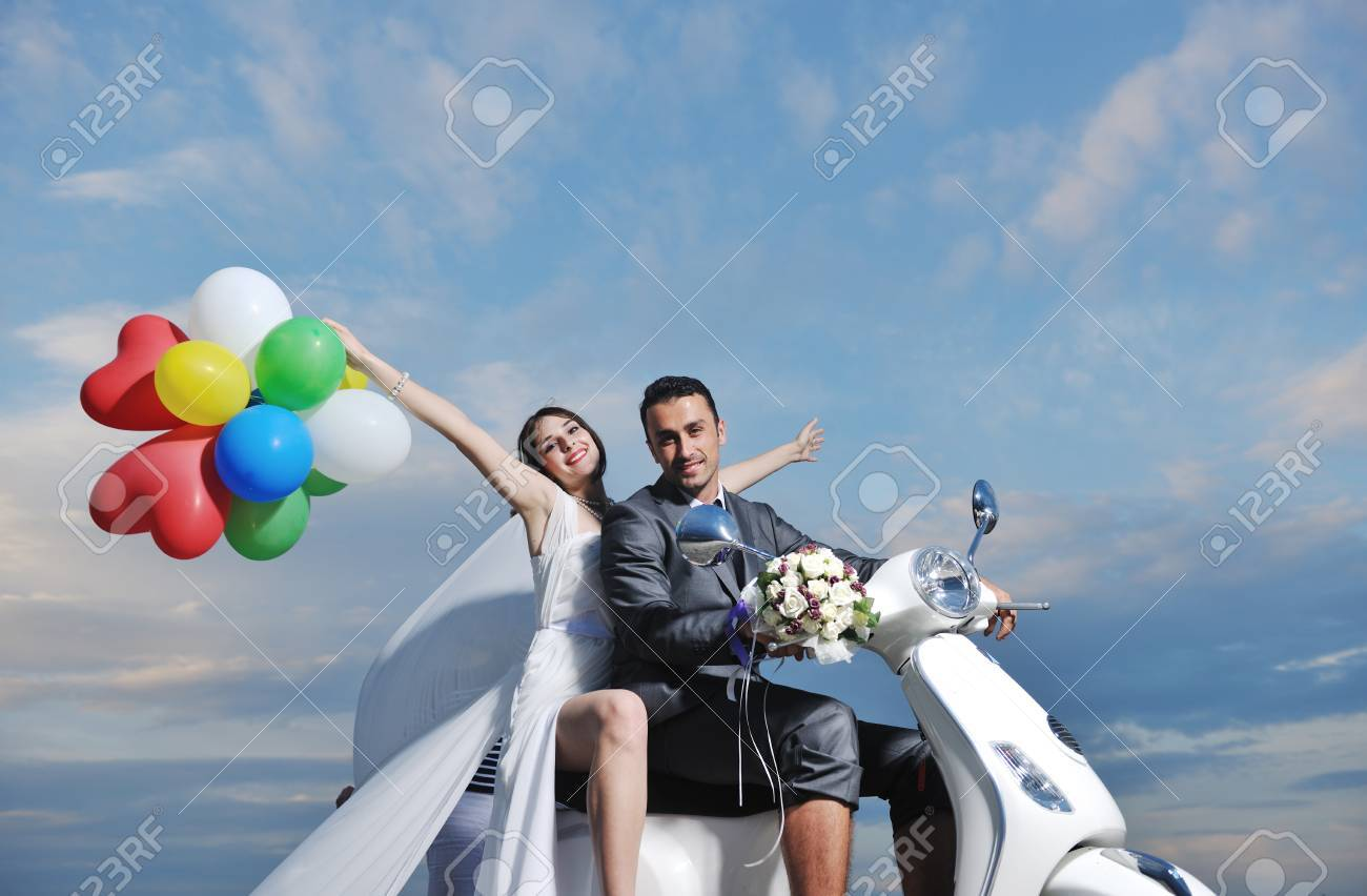 wedding sce of bride and groom just married couple on the beach ride white scooter and have fun Stock Photo - 9935998