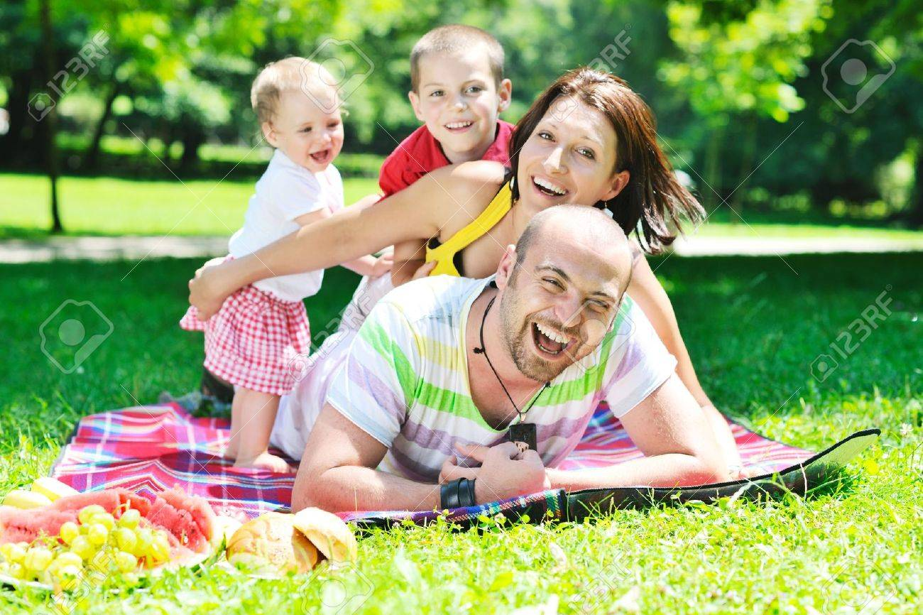 happy young couple with their children have fun at beautiful park outdoor in nature Stock Photo - 10415072