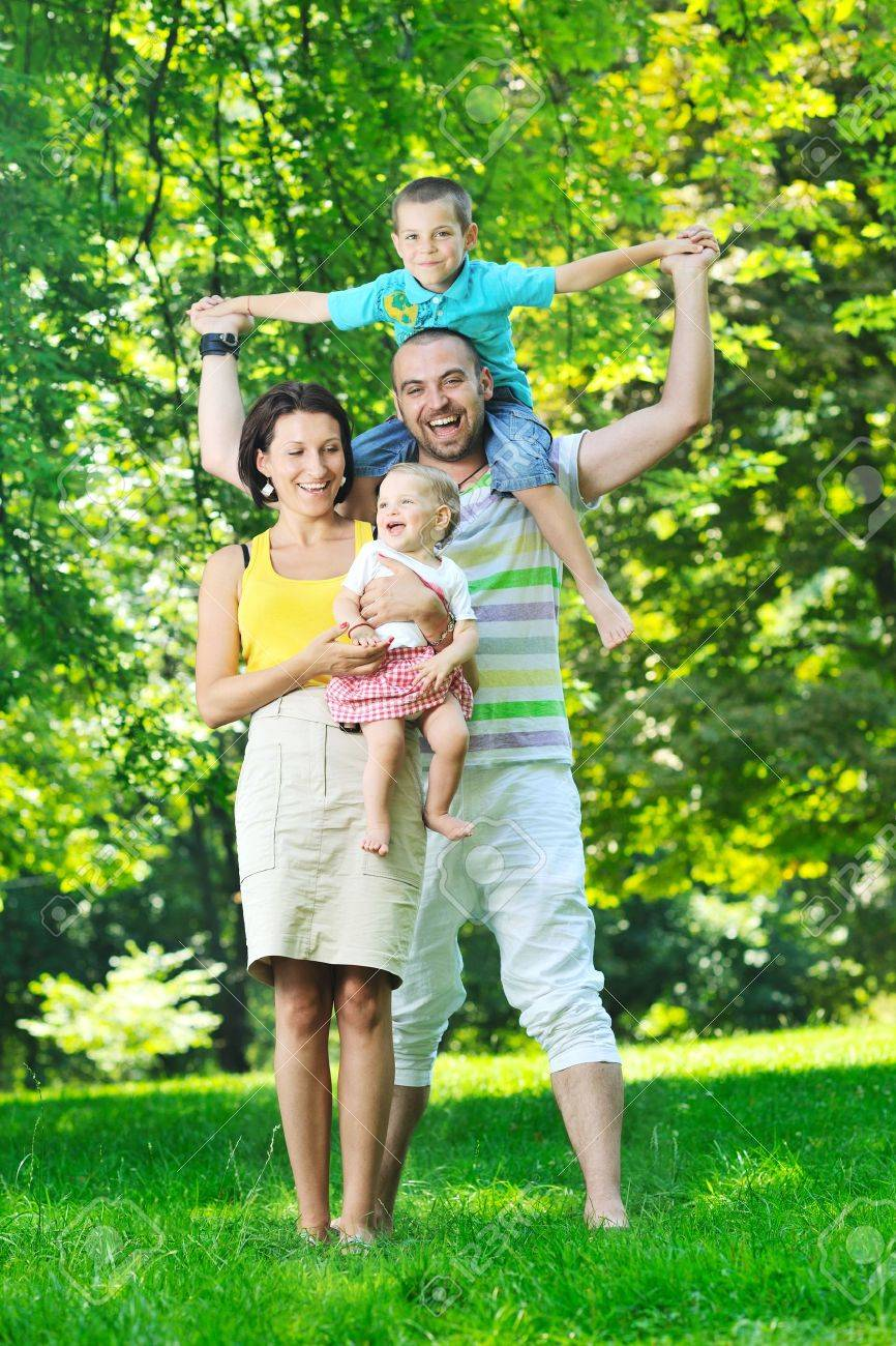 happy young couple with their children have fun at beautiful park outdoor in nature Stock Photo - 10415229