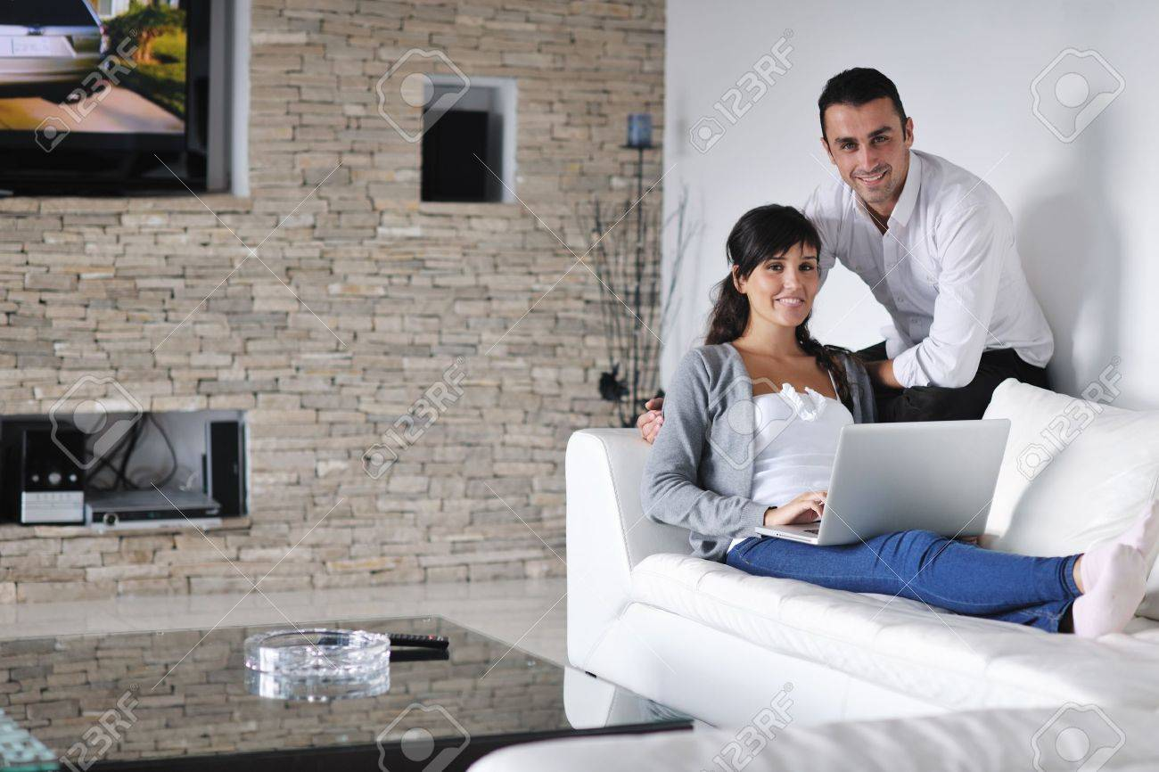 joyful couple relax and work on laptop computer at modern living room indoor home Stock Photo - 16392791