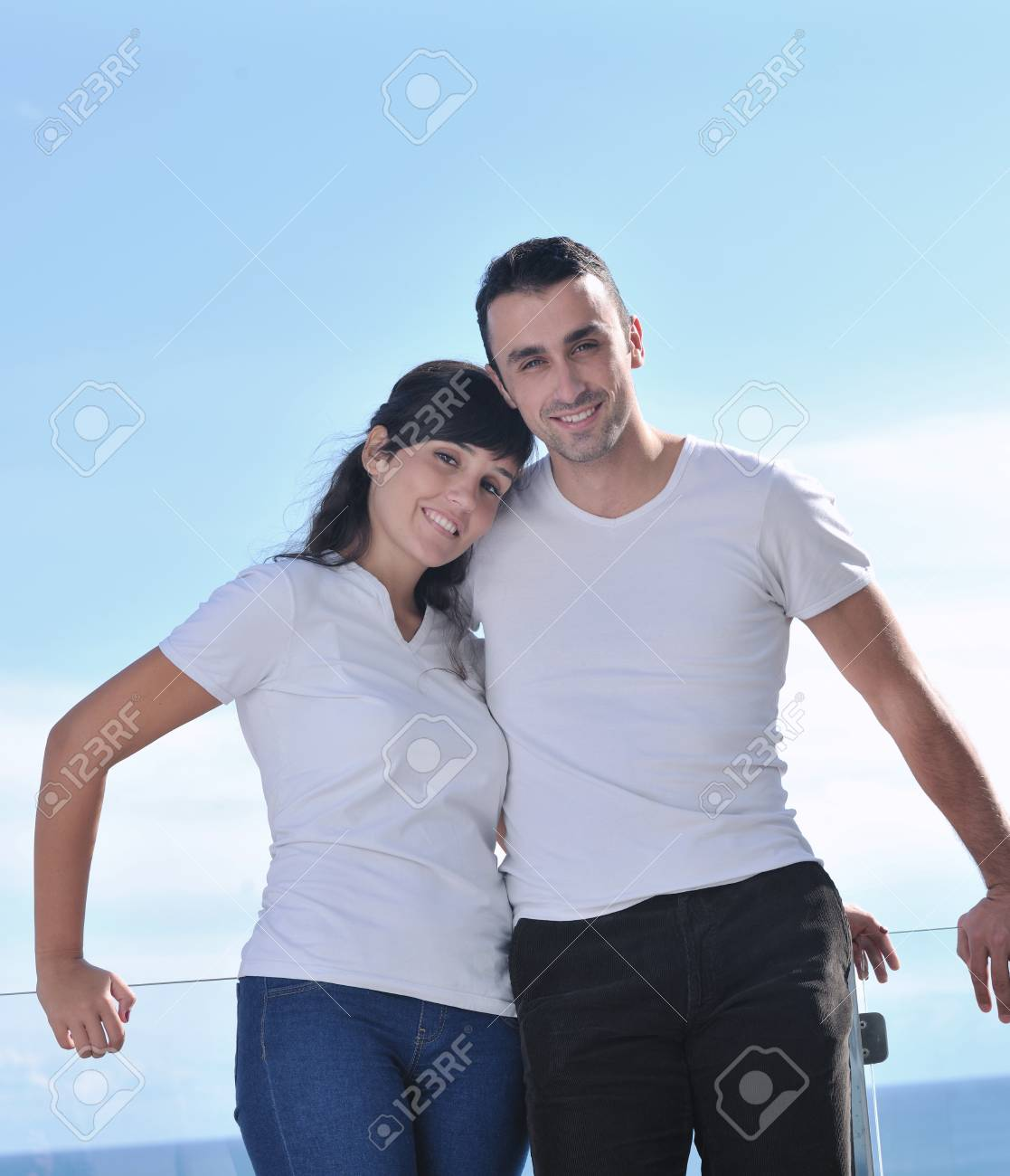 happy young couple relax on balcony outdoor with ocean and blue sky in background Stock Photo - 11398831