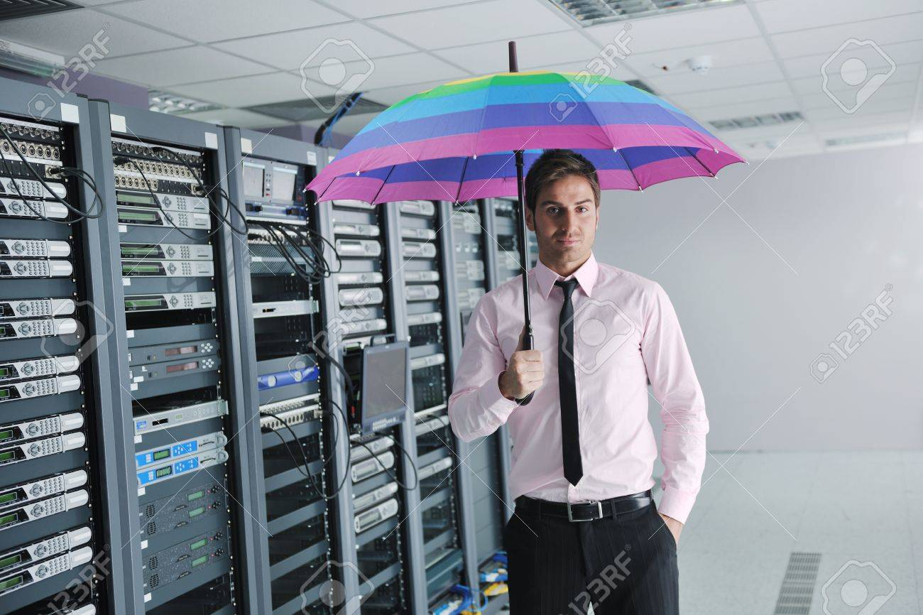 businessman hold  rainbow colored umbrella in server datacenter room  and representing security and antivirus sofware protection concept Stock Photo - 11718239