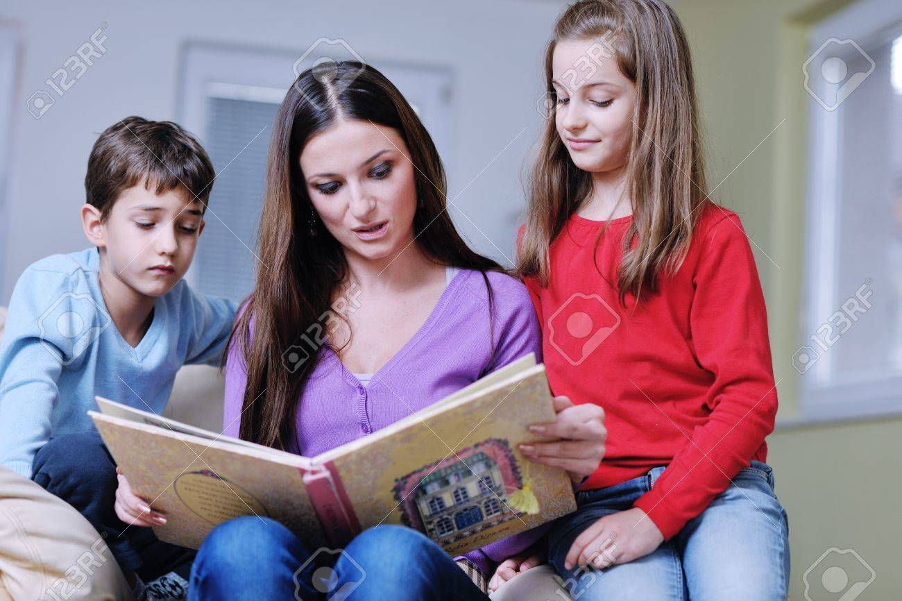 young mother read book to their kids at modern new home living room indoor Stock Photo - 12061164