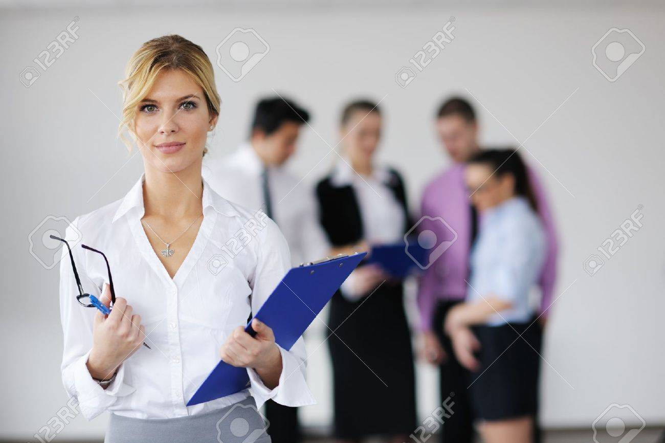 Successful business woman standing with her staff in background at modern bright office Stock Photo - 12565269