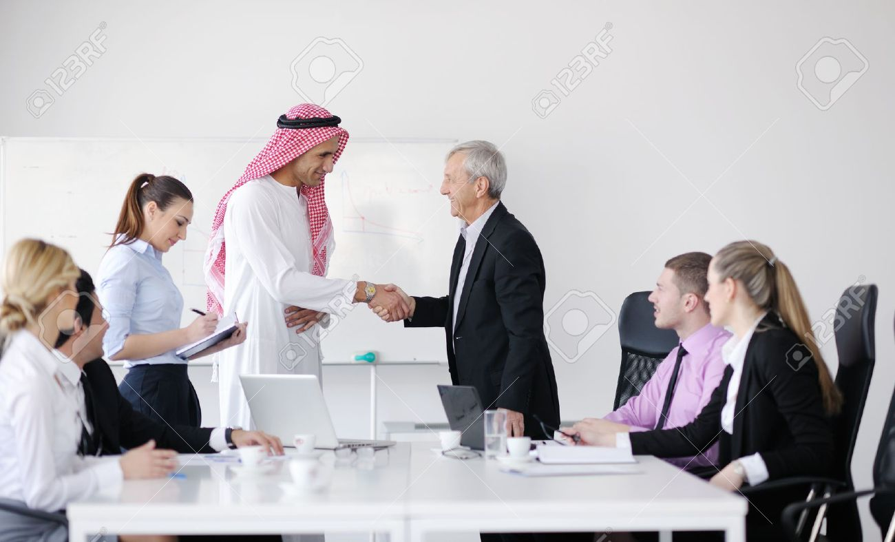 Business meeting - Handsome young Arabic  man presenting his ideas to colleagues and listening for ideas for success investments at bright modern office room Stock Photo - 12567702