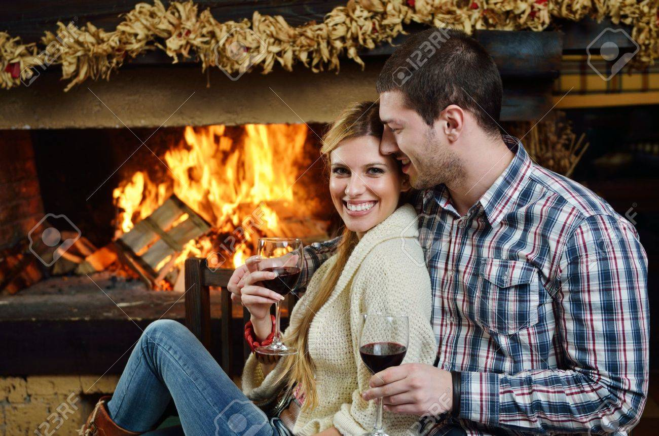 happy Young romantic couple sitting on sofa in front of fireplace at winter season in home Standard-Bild - 13112587
