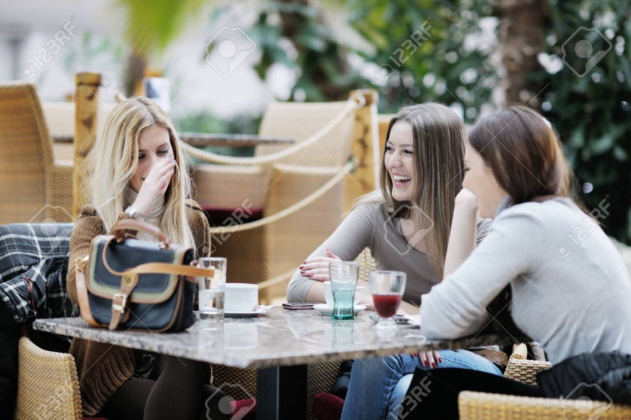 very cute smiling women drinking a coffee sitting inside in cafe restaurant Stock Photo - 13661980