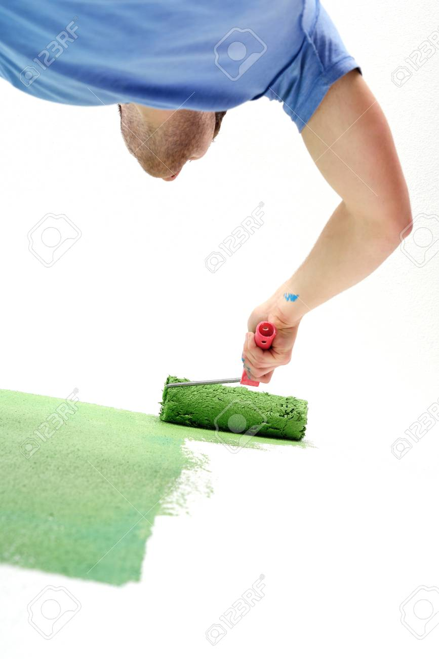 handsome young man paint in blue and green color  white wall of new home Stock Photo - 14169570