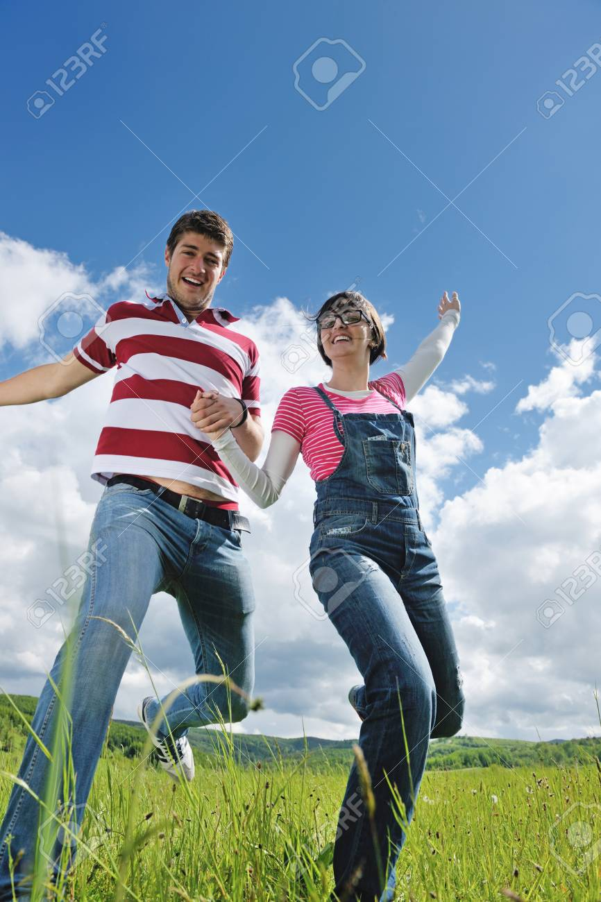 Portrait of romantic young couple in love  smiling together outdoor in nature with blue sky in background Stock Photo - 15275766