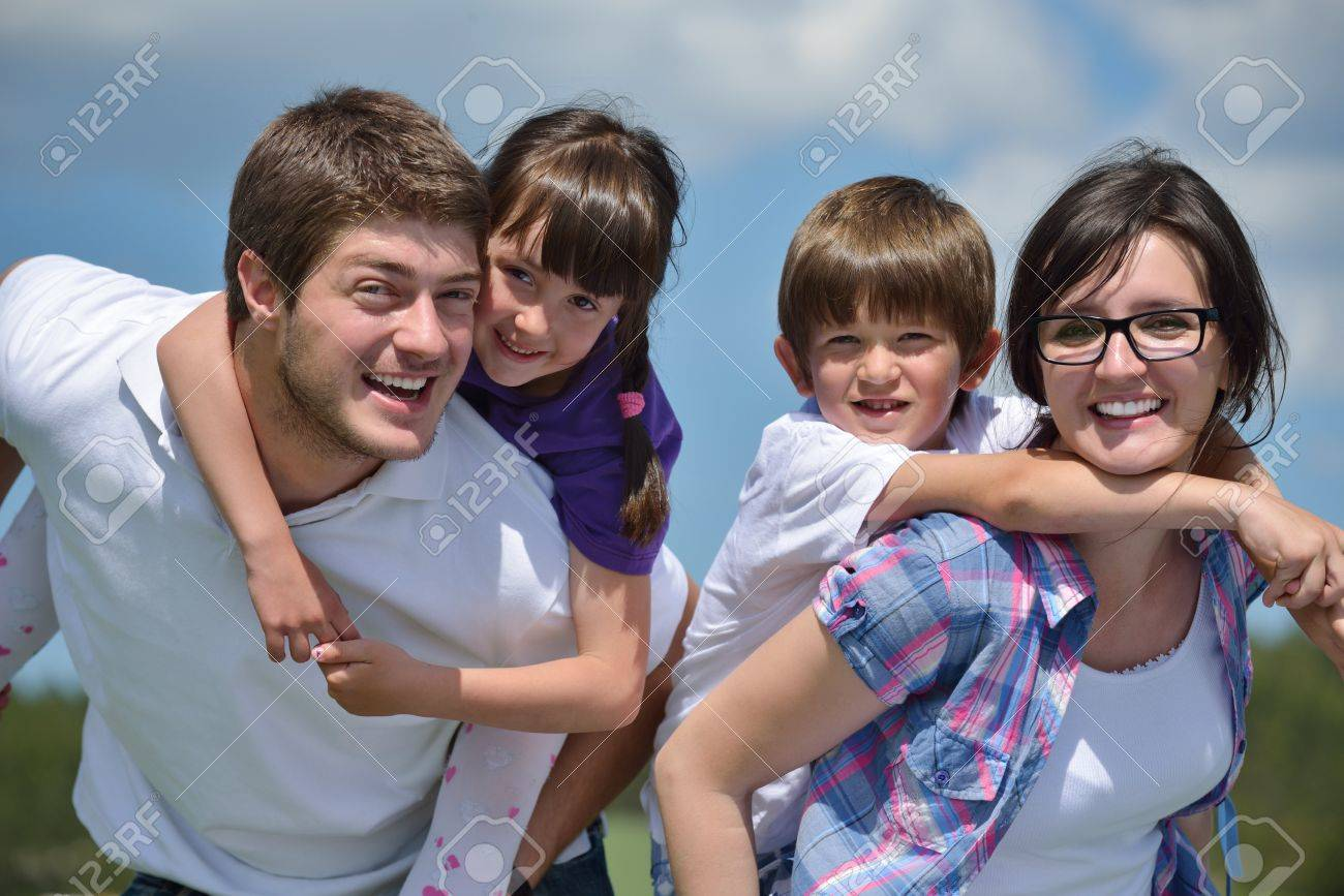 happy young family with their kids have fun and relax outdoors in nature with blue sky in background Stock Photo - 14592692
