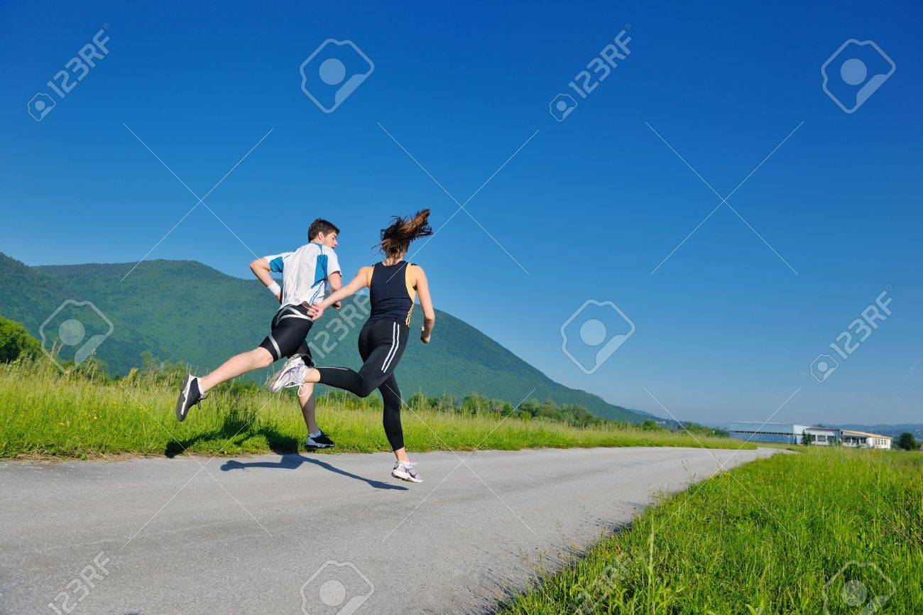 Young couple jogging in park at morning. Health and fitness. - 14739372