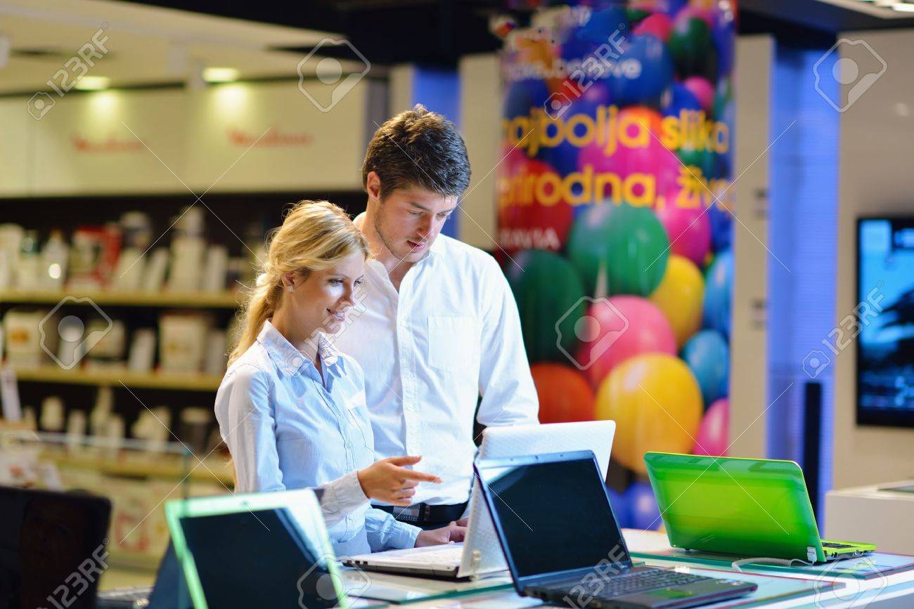 Young couple in consumer electronics store looking at latest laptop, television and photo camera Stock Photo - 15273005