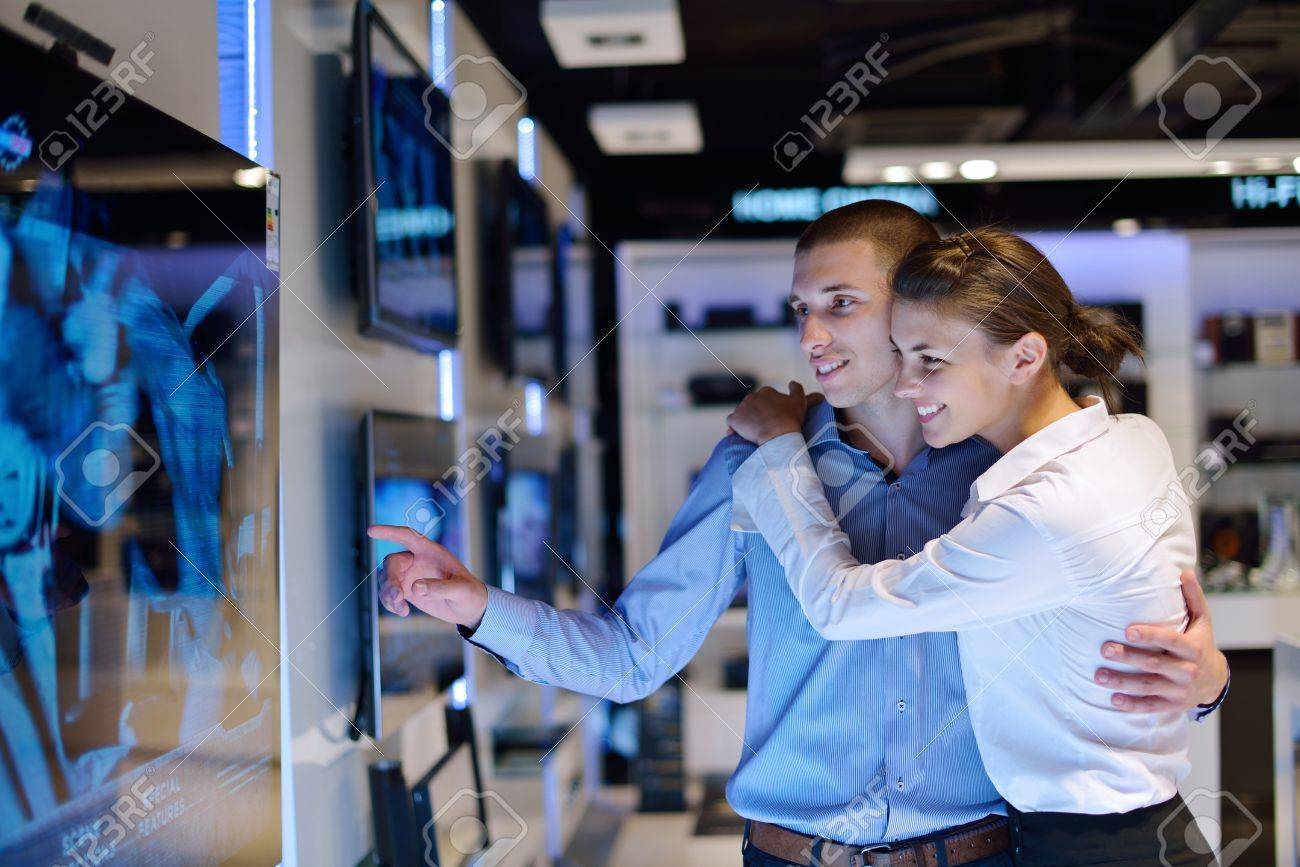 Young couple in consumer electronics store looking at latest laptop, television and photo camera to buy Stock Photo - 15273145