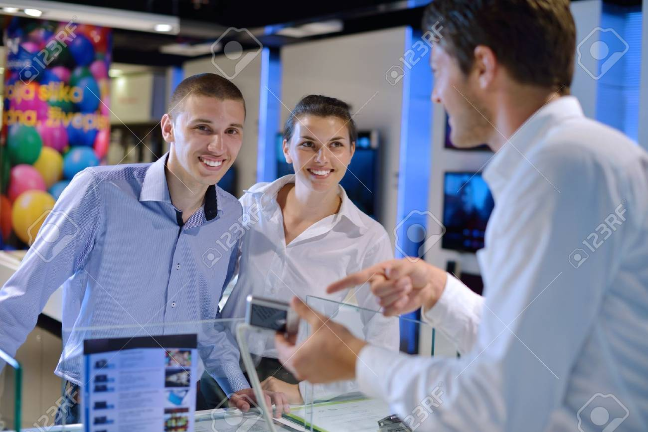Young couple in consumer electronics store looking at latest laptop, television and photo camera to buy Stock Photo - 14862481
