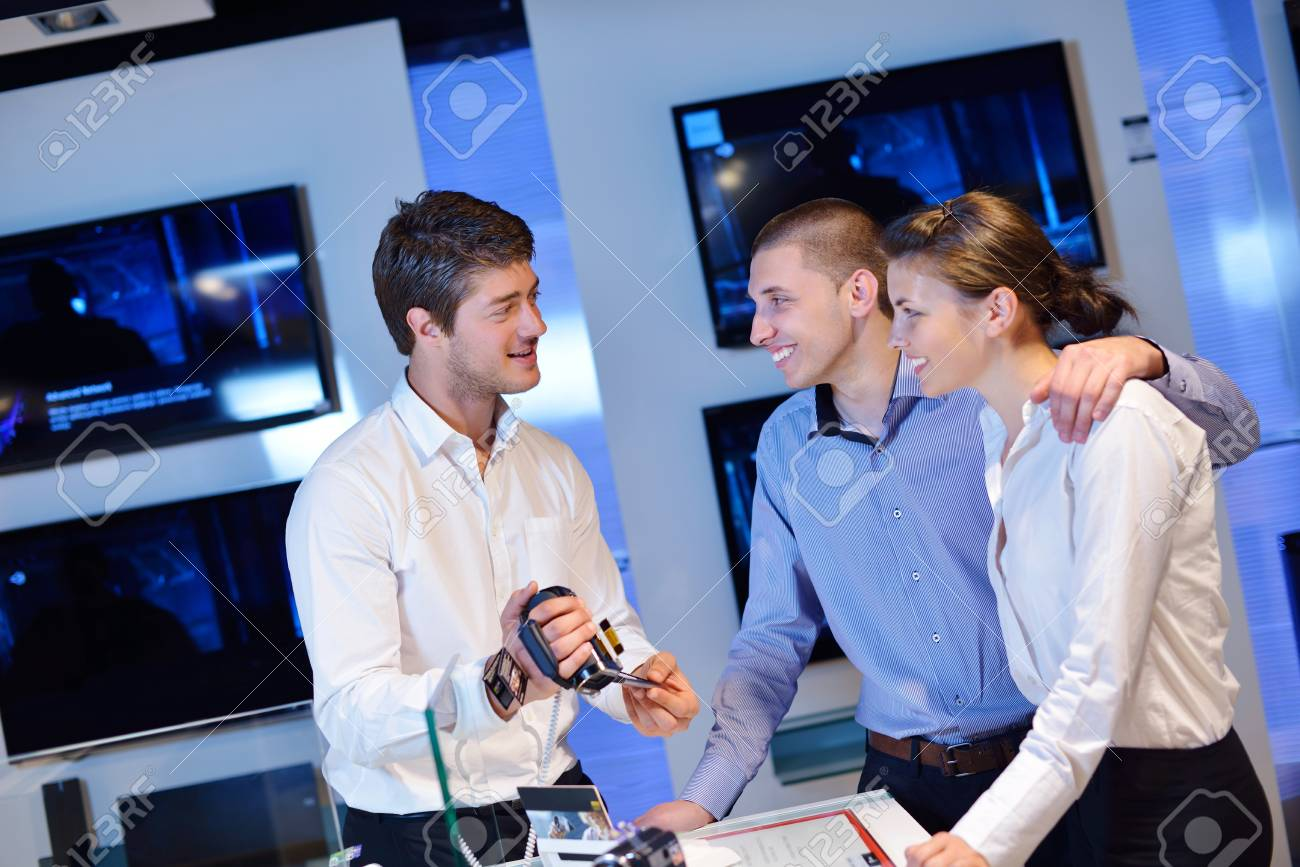 people in consumer electronics  retail store looking at latest laptop, television and photo camera to buy Stock Photo - 15242139