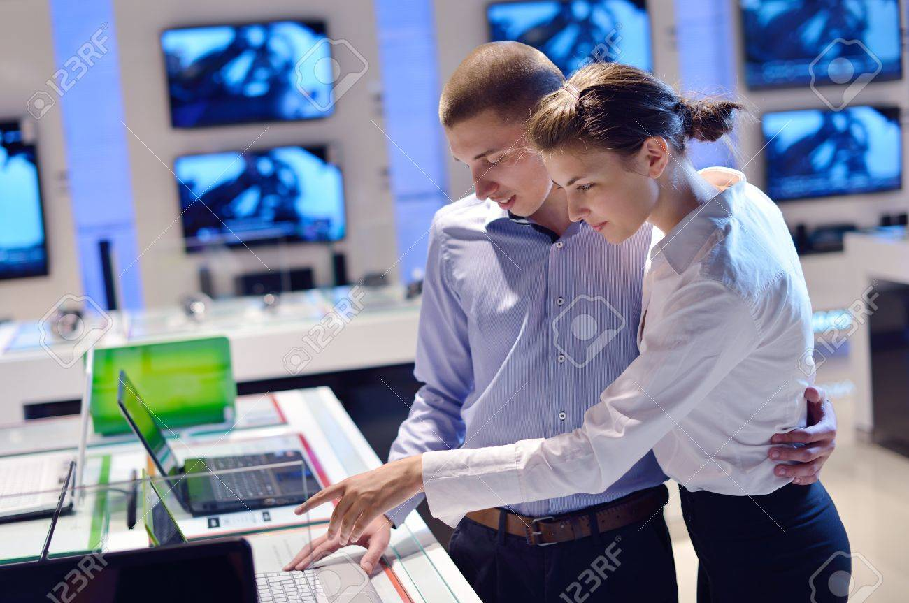 people in consumer electronics  retail store looking at latest laptop, television and photo camera to buy Stock Photo - 15241246