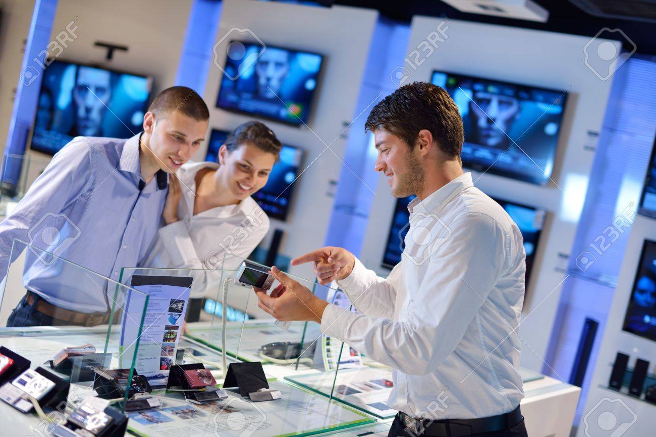 People In Consumer Electronics Retail Store Looking At Latest Laptop,  Television And Photo Camera To