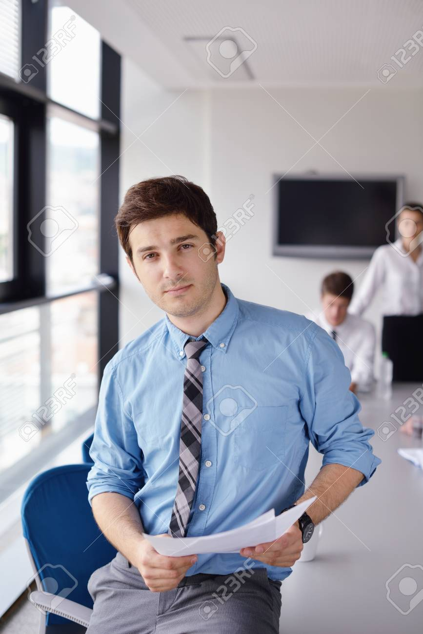 Portrait of a handsome young  business man  on a meeting in offce with colleagues in background Stock Photo - 15300919