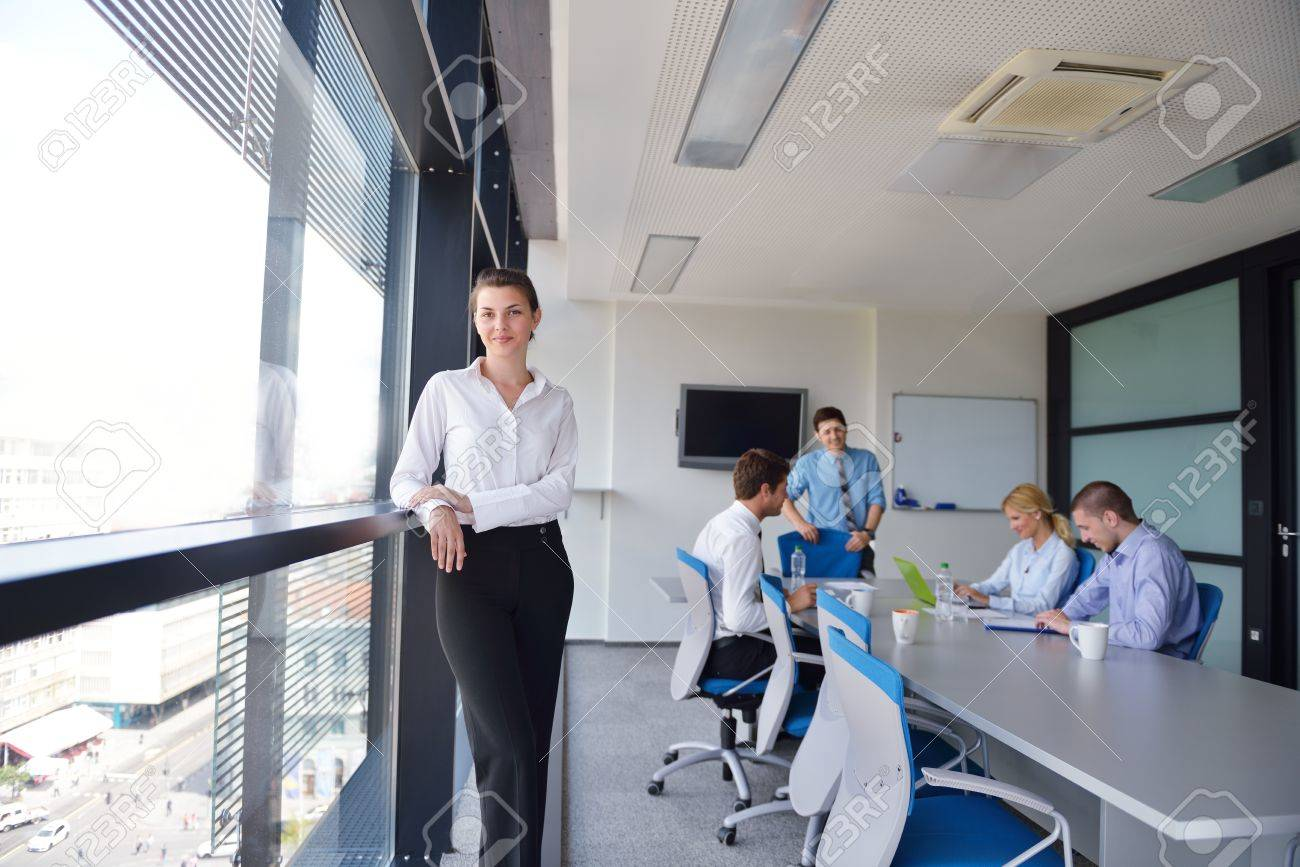 stock photo business woman with her staff people group in background at modern bright office indoors bright office