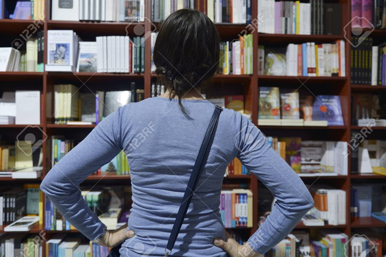Pretty female student standing at bookshelf in university library store shop  searching for a book Stock Photo - 15258403