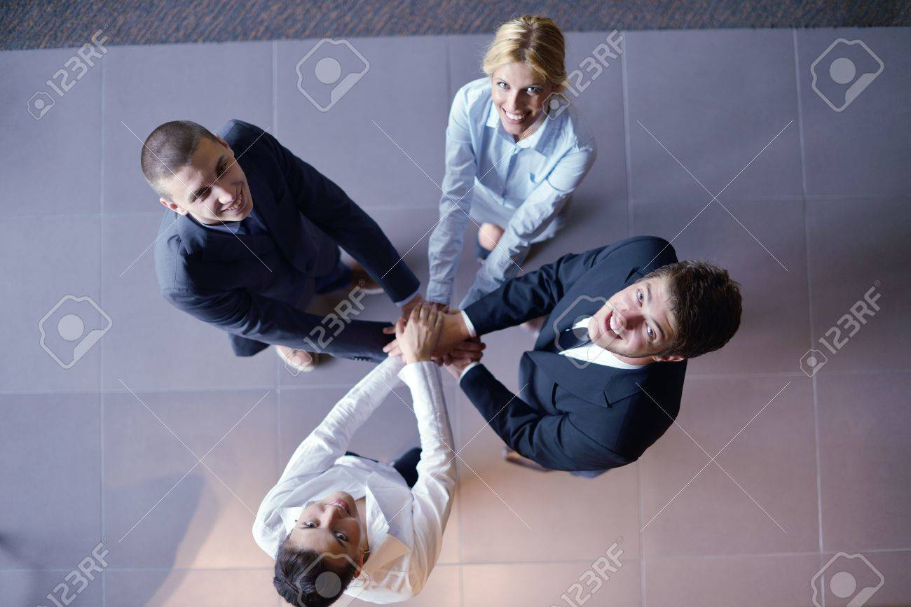 business people group joining hands and representing concept of friendship and teamwork,  low angle view Stock Photo - 15527289